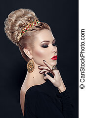 Profile view of a stylish blonde young woman with hairdressing, makeup, over black background.