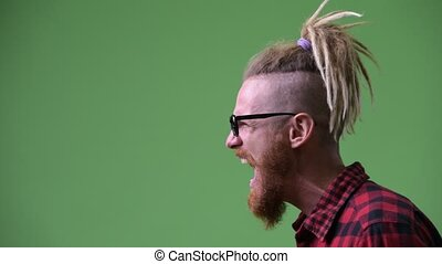 Profile view of angry bearded hipster man with dreadlocks...