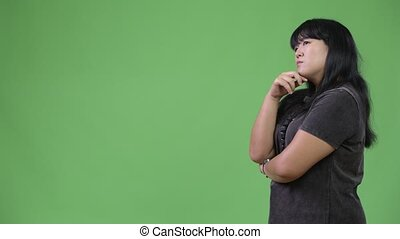 Profile view of beautiful overweight Asian woman thinking -...