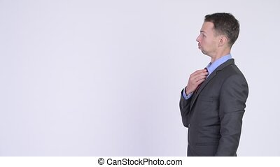 Profile view of businessman fixing his tie