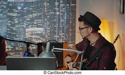 Profile view of handsome hipster singing into microphone and playing the guitar in home recording studio