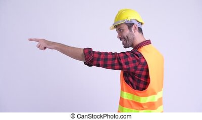 Profile view of happy bearded Persian man construction...