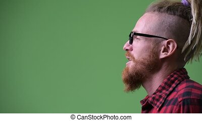 Profile view of happy handsome bearded hipster man with...