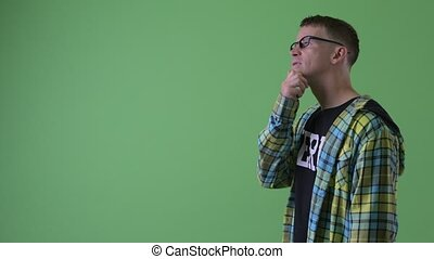 Profile view of happy nerd man thinking - Studio shot of...