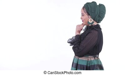 Profile view of happy young African Muslim woman thinking -...