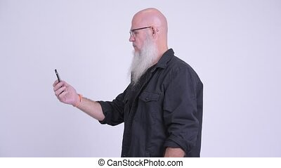 Profile view of mature bald bearded man with phone being taken away