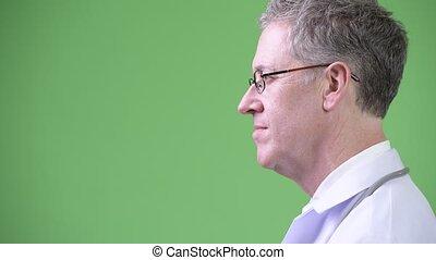 Profile view of mature man doctor wearing eyeglasses -...