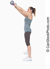 Profile view of ponytailed woman training with a kettle bell