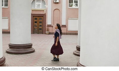 Profile view of pretty asian female walking along the columns outdoors. Rest, leisure concept. Slow motion