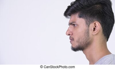 Profile view of young angry bearded Indian man screaming -...