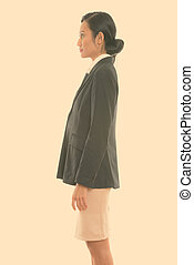 Profile view of young Asian businesswoman standing