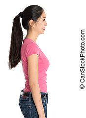 Profile view of young Asian girl in pink shirt and jeans with ponytail hair, standing isolated on white background.