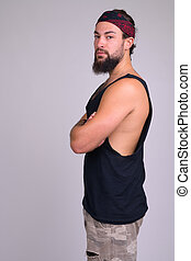 Profile view of young bearded handsome rebellious man looking at camera