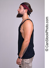 Profile view of young bearded handsome rebellious man