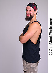 Profile view of young bearded happy rebellious man looking at camera
