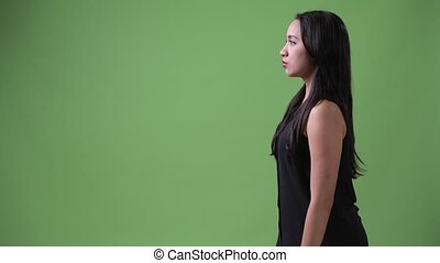 Profile view of young beautiful Asian businesswoman