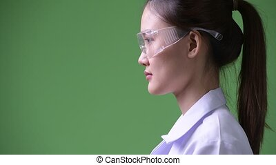 Profile view of young beautiful Asian woman doctor wearing protective glasses