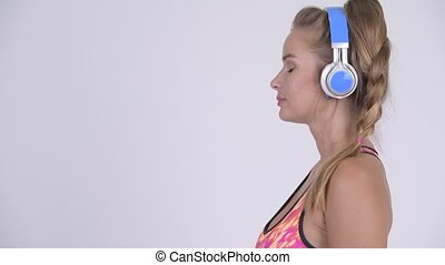 Profile view of young beautiful blonde woman listening to...