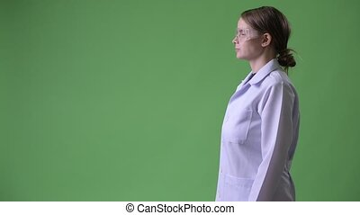 Profile view of young beautiful woman doctor wearing protective glasses