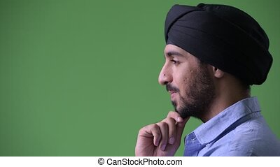 Profile view of young handsome bearded Indian businessman...