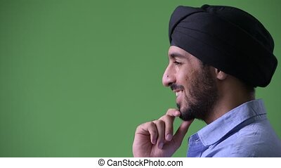Profile view of young happy bearded Indian businessman...