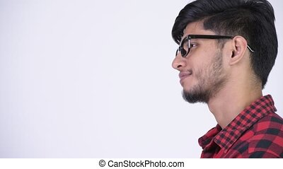 Profile view of young happy bearded Indian hipster man smiling
