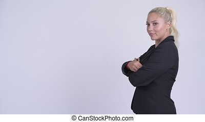 Profile view of young happy blonde businesswoman looking at camera with arms crossed