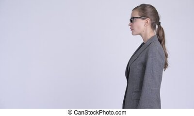 Profile view of young happy businesswoman looking up -...
