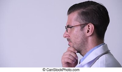 Profile view of young Hispanic man doctor thinking
