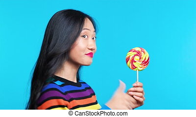 Profile view of young woman licking colorful lollipop on ...