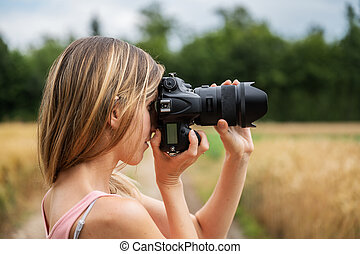 Profile view of young woman taking a photo of nature