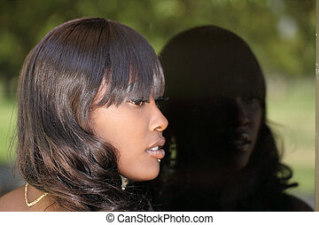 Profile young African American woman reflection window