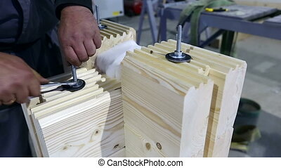 Profiled glued bars. View of man tightens fastener -...