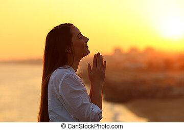 profilo, di, uno, donna pregando, a, tramonto