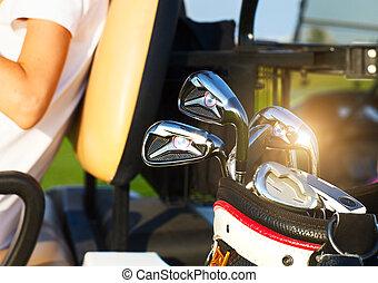 profissional, golfe, engrenagem, ligado, a, campo golfe, em, pôr do sol