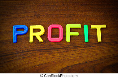 profit in colorful toy letters on wood background