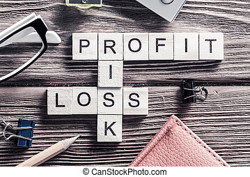 Profit loss and risk words on workplace collected of wooden...