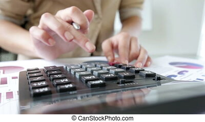 Profit - Close-up of businesswoman calculating company...