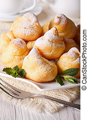 Profiteroles with powdered sugar close-up, vertical -...