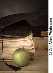 profs, bureau, à, livres, empilé, mortarboard, pomme, et, tableau, fond