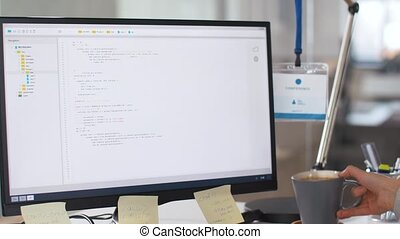 programmer at computer working and drinking coffee -...