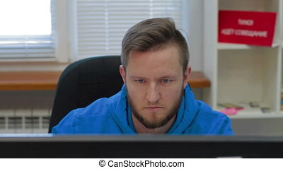 Programmer is working concerned on computer screen