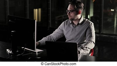 Programmer man is working in the office late at night overtime.