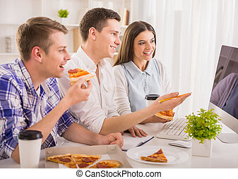 Group of young colleagues sitting at the table, eating pizza and working together.