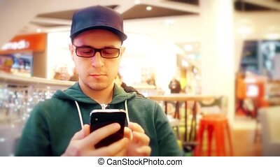 Programmer wearing black rim glasses taps on his mobile phone touchscreen in a cafe. 4K video