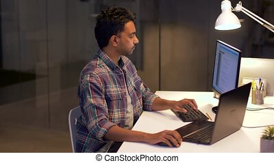 programmer with computer working at night office