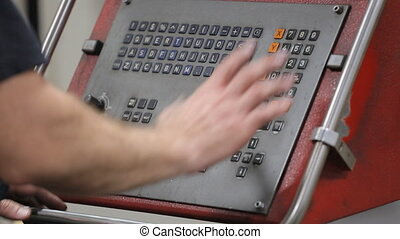 Programming a CNC machine. - Worker programming a CNC...