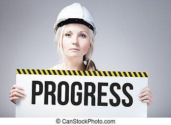 Progress sign held by worker