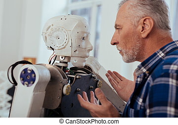 Serious smart engineer looking at the robot
