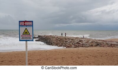 Prohibition sign for swimming on the beach during a storm, with people on the breakwater. Portugal